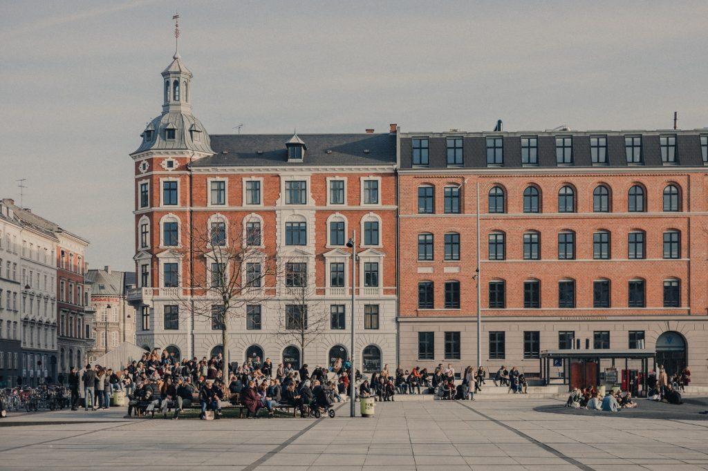 Israels plads i København på en solrig eftermiddag med en masse mennesker, der hænger ud